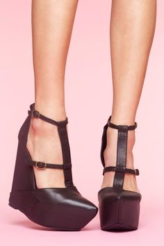 Zane Platform Wedge: Sky-high black leather wedges featuring buckled strap detailing and a covered platform. Pointed toe, zip closure at back. Leather interior, cushioned insole. Perfect paired with a body-con skirt and moto jacket! By Jeffrey Campbell.