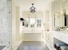 This is my favorite bathroom. I love the classic, clean look. Elegant but with unexpected details - light fixture, black tile. Carrera marble is elegant but not too overwhelming. Love the large windows, open feel. The vertical wood paneling on the walls is beautiful too,
