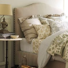 Pottery Barn's Raleigh Bed and Headboard features nailhead trim on the exterior edges of the bed and a graceful camelback silhouette.