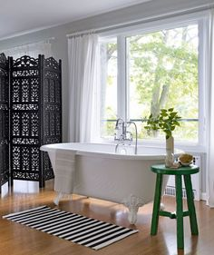 """Though this home's decor boasts some serious bargains, there were worthwhile splurges, too, like the Victoria + Albert claw-foot tub, positioned next to a picture window in the master bedroom. """"It's not a fancy house, but having a tub in our room feels so luxurious, and there's such a beautiful view,"""" marvels the owner."""