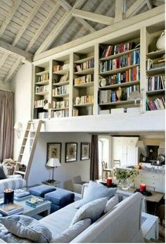 GREAT USE OF SPACE. Love the ladder. Darker, warmer setting with leather chairs. In an office with a reading nook underneath shelving.