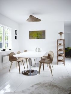 The kitchen of this Scandinavian summerhouse is full of fluid, flowing lines - in the chairs, lighting, and decorative bowls. The table and chairs are by Gubi from Denmark.