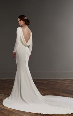 This long-sleeve Bellagio crepe designer bridal gown from Martina Liana is a statement piece. A bateau neckline carries through to sweep the low back, while modern buttons adorn the sleeves, skirt and cathedral train.