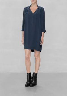 Made from lightweight Mulberry silk, this delicate dress features densely gathered fabric around the shoulders and draped fabric behind the neck.
