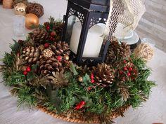 Detalhes de um arranjo de natal com vela e pinhas.