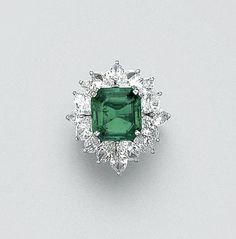EMERALD AND DIAMOND RING, CARTIER The emerald-cut emerald weighing 5.46 carats, framed by 16 pear-shaped and marquise-shaped diamonds weighing approximately 4.50 carats, mounted in platinum, size 6½, signed Cartier, numbered 89805. With red leather Cartier box.