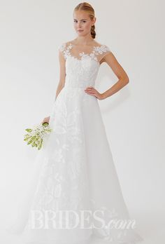 A #weddingdress with flower detail and an illusion neckline by @oscarprgirl | Brides.com