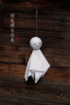"""""""Teru teru bōzu てるてる坊主 (shiny-shiny Buddhist priest) is a little traditional hand-made doll made of white paper or cloth that Japanese farmers began hanging outside of their window by a string. This amulet is supposed to have magical powers to bring good weather and to stop or prevent a rainy day. 'Teru' is a Japanese verb which describes sunshine and a 'bōzu' is a Buddhist monk.""""  — Wikipedia."""