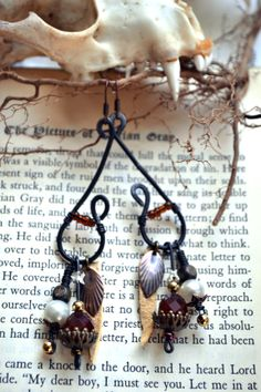teeny snake vertebra earrings with salvaged beads, thrifted leather and hand shaped wire.