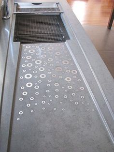 Concrete Works latest GEOTECH kitchen counter with custom drain board inlayed with stainless steel washers and a glide rail for a colander. The colour is a custom blended slate. This shows the limitless customization available with all their pre-cast products. *Photo supplied Floating Bathroom Vanities, Bathroom Vanity Cabinets, Bathroom Vanity Lighting, Granite Kitchen, Granite Countertops, Concrete Kitchen Counters, Countertop Materials, Concrete Bathroom, Very Small Bathroom