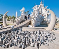 Sculptures in front of Wat Rong Khun in northern Thailand. Lots of hands reaching up from the underground on both sides of the pathway up to the temple.
