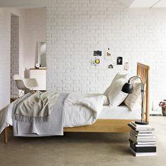Jasna sypialnia z ceglaną ścianą. / Bright bedroom with brick wall