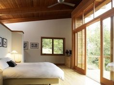 Bed on partial wall and wood ceiling