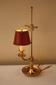 Made in France during the early 20th century, this artisan ally crafted Petit Bouillet table lamp is truly beautiful. Made of gorgeous bronze in the Empire style, this single-light table lamp features adjustable height and a hand-painted shade creating an elegant and classic look.