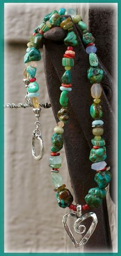 """Cathy Dailey:  Carico Lake & Tibetan Turquoise, Chalcedony, Calcite, Red Spiny Oyster Shell, Butter Jade,  Venetian Striped Beads from the Early 1900's;  Rose-cast Venetian """"White Hearts"""" - Early 1900's; Larimar, Green & Red Garnet, Peach Moonstone, slices of Tourmaline, Yellow African Opal &  Mexican Fire Opal with a sterling artisan crafted toggle."""