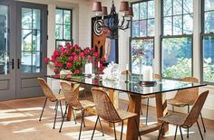 A chandelier from Laurin Copen Antiques in Bridgehampton hangs above a dining table crafted of reclaimed wood and glass. The set of midcentury wicker chairs was a lucky find from Paris's Clignancourt flea market. Design Eclético, House Design, Interior Design, Interior Architecture, Hamptons House, The Hamptons, Hamptons Decor, Dining Area, Dining Table