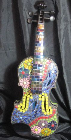 This is a broken violin that I mended and then covered with lovely vitreous glass and stained glass mosaic pieces. By mosaic tutor Tracy Johnson in Devon.