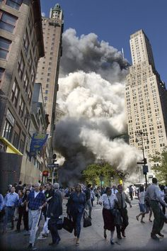 People flee the falling South Tower of the World Trade Center on Tuesday, September 11, 2001.
