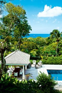 House tour: inside designer Kit Kemp's vividly coloured Barbados home : A view towards the garden, pool, dining pavilion and ocean beyond reveals the inspiration for the lime green and turquoise colours within the house.