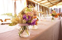 Image from http://wedding-pictures.onewed.com/match/images/125529/country-rustic-wedding-reception-floral-centerpieces.original.jpg.