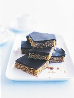 afternoon tea slice 1 cup (100g) rolled oats 1 cup (150g) plain (all-purpose) flour ½ cup (110g) caster (superfine) sugar ¾ cup (60g) desiccated coconut 2 tablespoons golden syrup 125g unsalted butter ½ teaspoon bicarbonate of (baking) soda 1 tablespoon hot water 300g dark chocolate, melted+