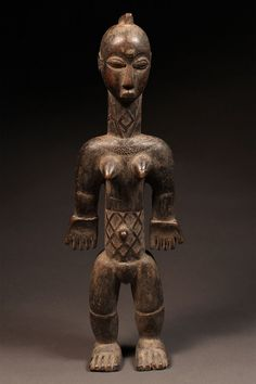 """Female Shrine Figure Bete Tribe, Ivory Coast Wood  H: 21"""" Inventory # 10362  Most well-known for the gre or nyabwa masks that presided over ceremonies held after armed conflicts, the Bete are also admired for their shrine figures, which were historically used to maintain harmony and balance between the ancestors, the otherworldly and worldly spirits, and the Bete people. This piece has tubular, muscular features and classic Bete scarification markings on the neck and torso."""