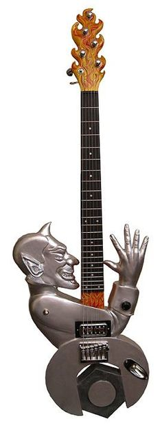 """Meet Mark Behme from Silver Spring in Maryland, USA. He is a painter, sculptor and guitar builder. Here are some of his carved guitars. This is: Nut Job 2008 Mahogany, maple, ebony, Steinberger tuners, Schaller roller bridge,TV Jones Powertron Plus pickup 38: x 12"""" x 4"""" The theme comes from radiator cap ornament for hot rods of the 50's vintage. Maple and ebony through-body neck and mahogany body painted silver. Head stock carved as flames."""