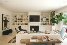 White living room with built-in shelving, black, light blue furniture - Rip + Tan Profile: Kelly Sawyer Patricof