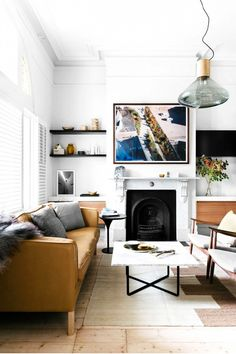 Leather sofa in eclectic living space with black fireplace and hanging light fixture