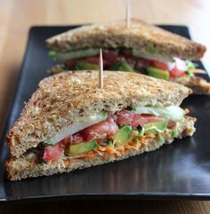 Hummus and avacado veggie sandwich. Includes carrot, alfalfa sprouts, tomato, cucumber.