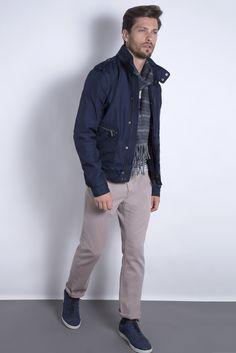 Jaqueta bomber de nylon marinho, tricô com mix de listras, cachecol de lã e calça cáqui five pockets. O tênis índigo finaliza o look casual com estilo.