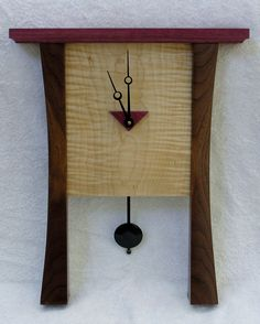 CONTEMPORAY CLOCK MADE FROM WALNUT, CURLY MAPLE, AND PURPLE HEART. LOOKING TO BE ADOPTED BY A NICE FAMIULY THAT WANTS TO BE ON TIME FOR CHURCH.