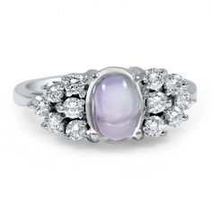 Twelve glittering round brilliant accents sit on either side of a breathtaking moonstone cabochon in this one of a kind Retro-era piece. The chic design and unique center stone make this an exceptional and unforgettable ring (approx. 0.36 total carat weight).