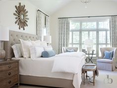 Gray and blue bedroom features a wood sunburst mirror over a gray linen tufted bed dressed in white and blue bedding and a blue velvet bolster pillow flanked by 3 drawer curvy nightstands topped with taupe lamps situated under windows dressed in white and gray trellis curtains in Braemore Fioretto Sprout Fabric as well as an oval French cane bench placed at the foot of the bed.