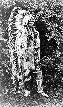 Umapine (Wakonkonwelasonmi), a Cayuse chief; full-length, standing, wearing a feathered headdress. Halftone of photograph by Joseph K. Dixon, September 1909.
