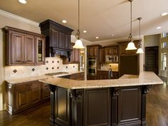 Two tone wood kitchen with large bar style island, tile back splash and cream color granite counters