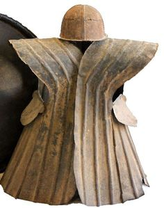 Unique set of sheet metal armor used by natives on the Indonesian island of Nias. Armored vest, hinged down the back, with a ridge of spiked sheet metal down the spine. Thin handmade armor was used to repel enemy arrows during the many civil wars fought amongst the islands inhabitants. Also an iron battle helmet (takula tofao),  armor measures 24 inches wide, and 26 high, and shield is 32 inches in diameter.