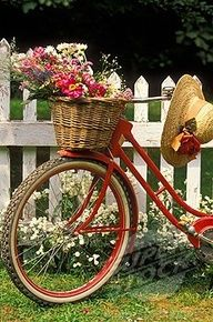 Bicycle with a flower basket and a sun hat next to a white picket fence
