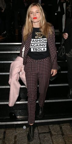 Georgia May Jagger wears a plaid suit, graphic t-shirt, pink sweater, ankle booties, and an orange lip