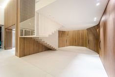 a warping wooden skin and floating steel stairs dramatically reshape this two-floor apartment.