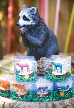 DIY painted animal figurines glued to a mini tree stump — cute kids room decor or party favors