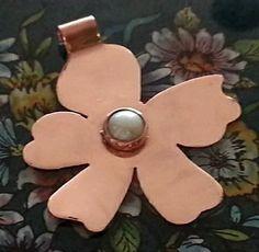Flor irreverente con perla. Técnica de calado, y engastado en cobre.