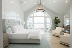 White Contemporary Bedroom With Round Windows  To make a stunning frame for this master bedroom's harbor view, the designers customized a round set of windows and doors that practically fill up one entire wall. The pale palette of the room's interior also draws attention to the outdoor scenery.