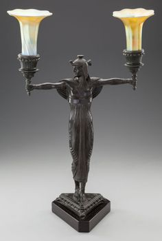 AN EGYPTIAN REVIVAL BRONZE AND IRIDESCENT GLASS FIGURAL TWO-LIGHT LAMP, circa 1900.