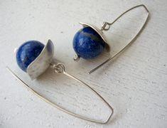 Boucles d'oreilles style simple et propre, composés d'un crochet long argenté et d'un pendentif réalisé avec une poignée d'argent avec le côté de 1,2 mm, couper et en forme de marteau, la pierre est une sphère de lapislauzuli de 11 mm de diamètre. Les pierres disposées donnent la