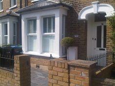 square bay window Victorian house.. Slate garden..topiary planter.. White shutters , white door