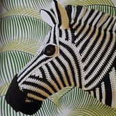 The direction of the zebra's stripes is determined by the shaping of the head, crocheted in rounds and short rows. The mane is made by attaching tassels to the stitches and brushing through the yarn to tangle the fibres and help it stand on end.