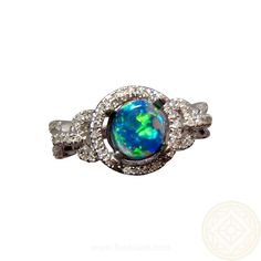 Genuine Black Opal ring for women with multi diamonds and fancy ring setting in 14k Gold.  The round Lightning Ridge Opal has a body tone of N2 which highlights the very bright Blue color and the small amount of Green and looks beautiful in the fancy link band with pave set diamonds.  A halo of Diamonds surround the Black Opal to finish off the bright colors and lively play of color and to add plenty of sparkle to the ring making it ideal as an engagement ring.