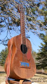 """Metal Guitar by Metal Petals Garden Art;  Tuners are recycled dimes, strings are rebar wire, the bridge is the identifying tag off of a old oil tank (year 2000) and the strap is a recycled leather belt. Guitar rests on a round base.  34"""" high, 12"""" wide"""