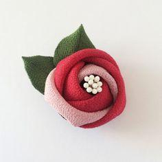 ご好評いただいている「まるっこ椿」をレトロモダンなデザインで髪飾りにいたしました。可愛いらしいまるっこい二輪の椿が、七五三やお正月など、お着物のコーディネートに花を添えてくれると思います♪裏面には「クリップ」をお付けしております。下がりは取り外し可能ですのでお花だけの形でもお付けいただけます。-------------------------------------------------------*大きさ 全体 :横)約9cm、縦)約9.5cm 椿の花:直径)大きい方:約4.2cm、小さい方:約3.2cm 下がり:約6cm*素材 一越ちりめん、ペップ、鈴※通常受注制作となっております。※手作業のため、多少の個体差がありますことをご了承ください。-------------------------------------------------------*色違いもございます☆朱x白 https://www.creema.jp/item/2854632/detail/★白x朱 https://www....